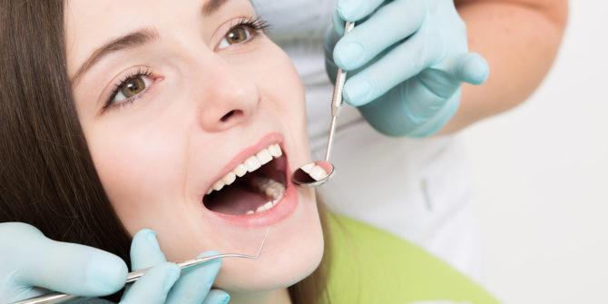 Женщина на поцедуре по чистке зубов Air Flow