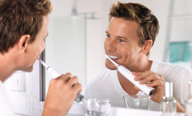 Мужчина чистит зубы электрощеткой