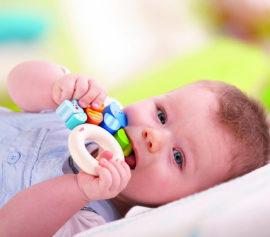 Ребенок играет с прорезывателем во время прорезывания зубов